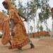 ঢাকার কাছে একটি চাতালে ধান শুকানোর কাজ করছেন কয়েকজন নারী।