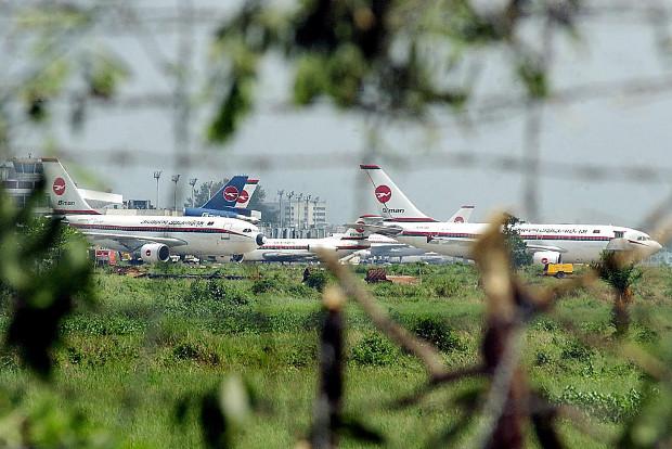 Planes belonging to Biman Bangladesh Airlines are visible through storm-damaged trees at Zia International Airport in Dhaka, April 23, 2003.
