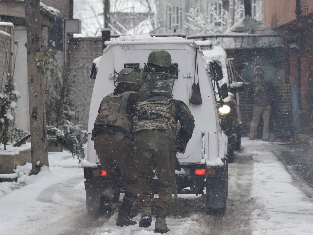 Paramilitary security personnel hide behind a bullet-proof vehicle during a gunfight with suspected LeT militants near their camp in Srinagar, Feb. 12, 2018.  [Sheikh Mashooq/BenarNews]