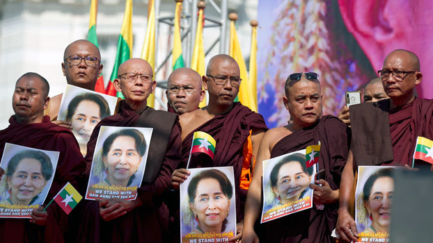 Buddhist monks hold portraits of Myanmar leader Aung San Suu Kyi while standing on a stage to pray during a rally in front of City Hall in Yangon, Dec. 10, 2019. [AP]