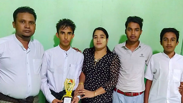 Rohingya student Muhammad Ayaz (second from left) holds a trophy he received in recognition of his scholastic achievements as he stands beside his parents and brothers at their home in Buthidaung town, in Myanmar's Rakhine state, in an undated photo. [Photo courtesy of Muhammad Ayaz's family]