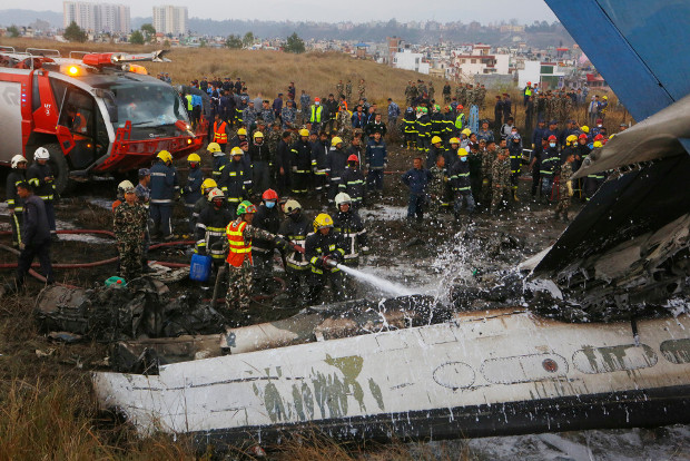 Nepalese firemen spray water on the debris of crashed US-Bangla Flight 211, March 12, 2018. [AP]