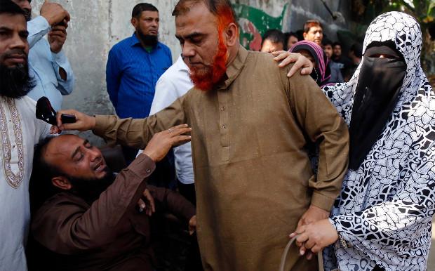 Relatives console a man after a massive fire killed at least 67 people in Dhaka's Chawkbazar neighborhood, Feb. 21, 2019. [Megh Monir/BenarNews]