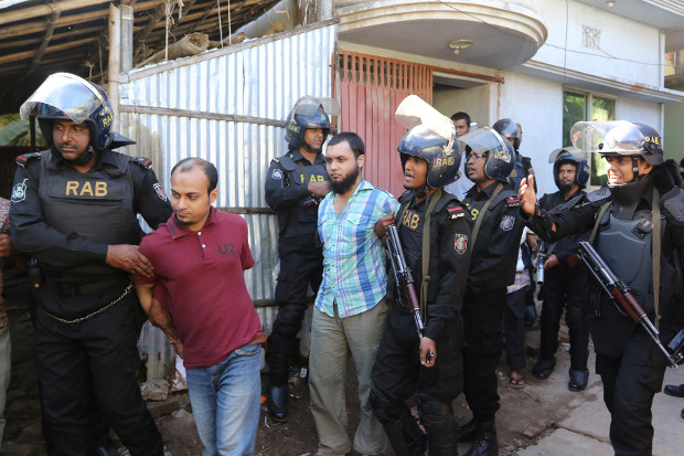 Members of the Rapid Action Battalion arrest suspected members of a banned extremist group in Chittagong, now officially known as Chattogram, Dec. 8, 2016. [AFP]