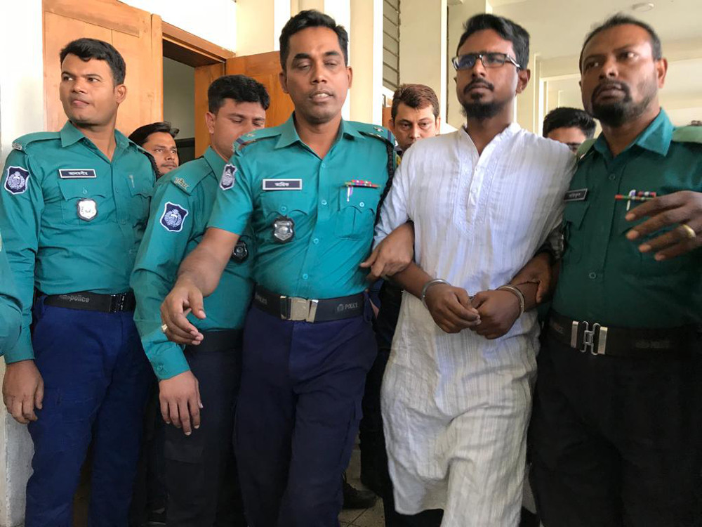 Bangladeshi police officers escort Shariful Islam (alias Khaled) out of an anti-terrorism court in Dhaka after a judge sentenced him and six other defendants to death for the Holey Artisan café attack, Nov. 27, 2019.