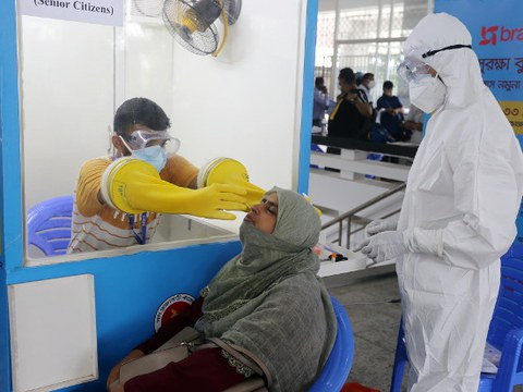 Medical workers collect samples for a COVID-19 test at a temporary isolation center in Dhaka, July 20, 2020.