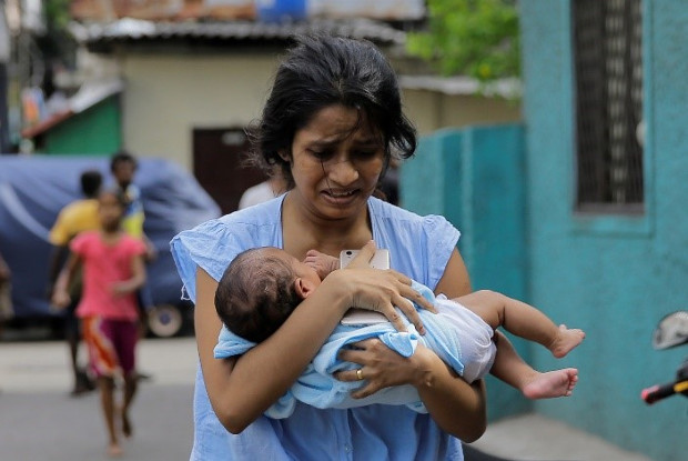 A Sri Lankan woman living near St. Anthony's Shrine church runs for safety with her infant after police found explosive devices in a parked vehicle in Colombo, Sri Lanka, April 22, 2019, a day after nearly 300 people were killed in Easter Sunday bombings that targeted churches and luxury hotels in the country. [AP]
