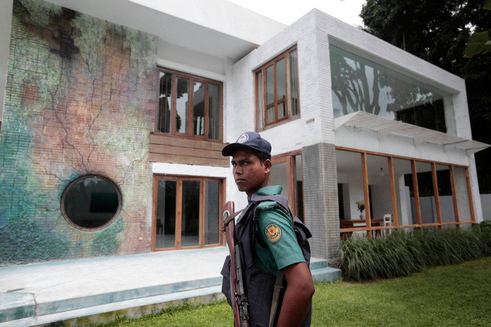 A Bangladeshi policeman stands guard in front of the building that once housed the Holey Artisan Bakery, on the first anniversary of a deadly hostage crisis at the upscale restaurant in Dhaka, July 1, 2017. [AP]