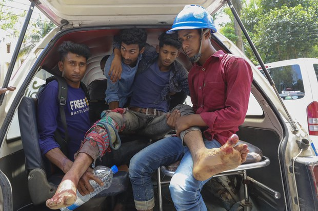 An injured man is loaded into a van after police fired on people protesting over wages and benefits at a Chinese-financed power plant in Banshkhali sub-district, southeastern Bangladesh, April 17, 2021.