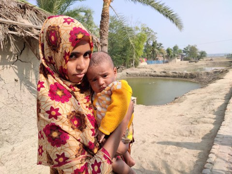 Jannatun Khatun stands with her 2-month-old son in front of their home in Satkhira district, southwestern Bangladesh, Dec. 31, 2020
