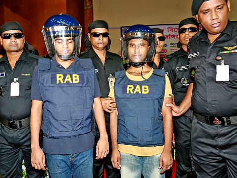 Rapid Action Battalion officers present two suspected members of Jamaat-ul-Mujahideen Bangladesh after they surrendered in Bogra and pledged to leave the militant organization, Oct. 5, 2016.