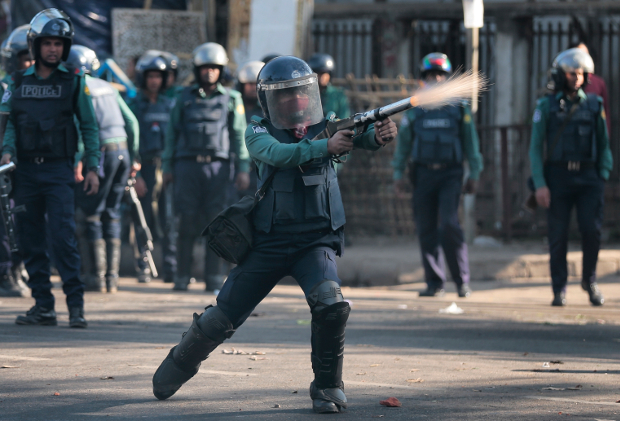 A Bangladeshi police officer fires tear gas at demonstrators protesting against plans to build a coal-fired power plant, in Dhaka, Jan. 26, 2017. (AP)