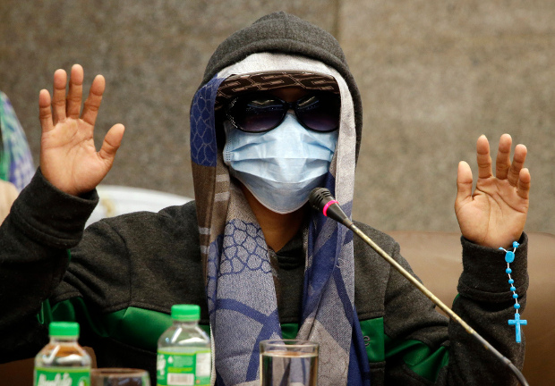 An eyewitness concealing his identity gestures during a Philippine senate investigation in Manila into the death of Kian Loyd Delos Santos, a 17-year-old student who was killed in an alleged drug crackdown, Sept. 5, 2017. (AP)