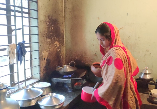 Shipa Akhter cooks in a kitchen that she and her husband share with another family at their home in Dakshinkhan, Bangladesh, July 20, 2019. [Jesmin Papri/BenarNews]