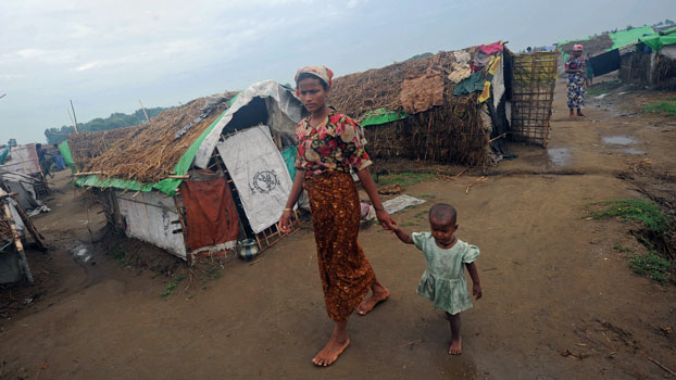 A Rohingya woman and her child walk in front of tents at the Mansi IDP camp, on the outskirts of Sittwe in western Myanmar's Rakhine state, May 15, 2013. (AFP)
