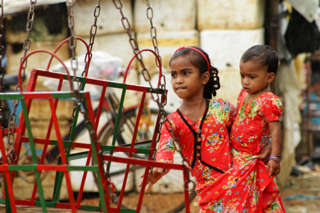 A Rohingya girl helps her sister get on a ride at the Eid-ul-Adha fair at the Kutupalong refugee camp in Ukhia, Cox's Bazar, Aug. 22, 2018. (Sharif Khiam/BenarNews)
