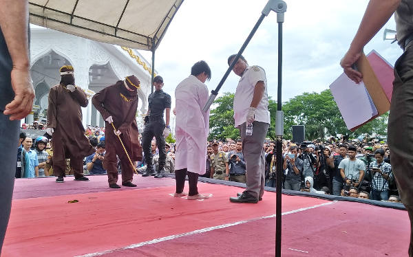A medic checks on a man undergoing caning after being convicted of gay sex in Banda Aceh, Indonesia, May 23, 2017. [Nurdin Hasan/BenarNews]
