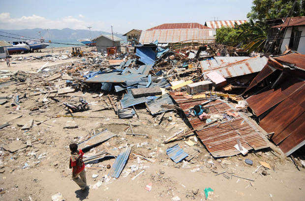 A man walks near collapsed homes in Wani II village of Donggala Regency, days after a powerful earthquake and a tsunami struck Central Sulawesi province, Oct. 2 2018. [Keisyah Aprilia/BenarNews]