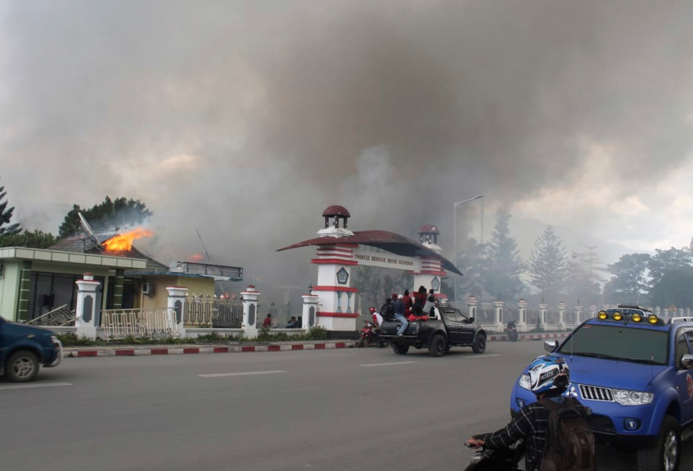 Residents drive past a burning government building during a protest that turned violent in Wamena, Papua province, Indonesia, Sept. 23, 2019. [AP]