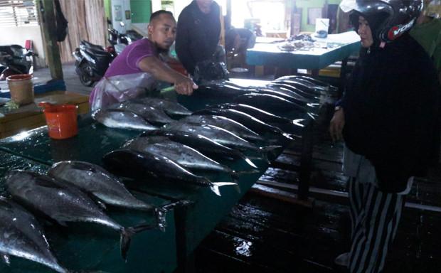 A fishmonger (left) sells fish to a customer at a market in Ranai, in Indonesia's Natuna regency, Dec. 6, 2019. [Nosa Normanda/BenarNews]