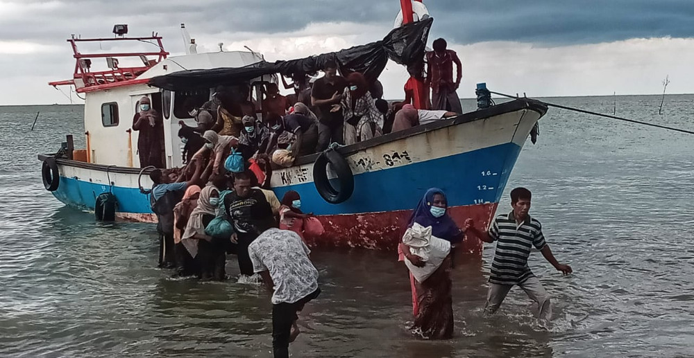 Rohingya women are helped ashore in North Aceh, Indonesia, June 25, 2020. [Muzakkir Nurdin for BenarNews]