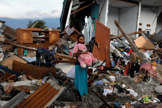 A woman holds a stuffed rabbit after it was found at her destroyed home, where she said she had lost her three children in earthquakes and a tsunami that battered Palu, in Indonesia's Central Sulawesi province, Oct. 7, 2018. [Reuters]