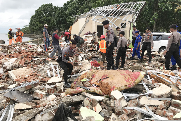 Police take part in a search for tsunami victims amid collapsed building in Pandeglang regency, Banten province, Dec. 24, 2018. [Keisyah Aprilia/BenarNews]