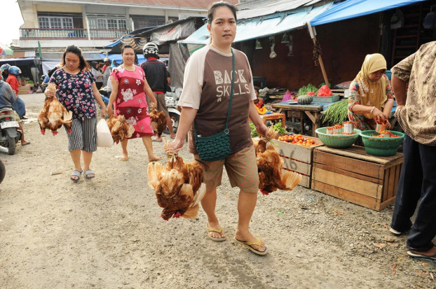 Palu residents carry chicken they bought from a market which reopened days after a powerful quake and tsunami battered Indonesia's Central Sulawesi province, Oct.  4, 2018. [Keisyah Aprilia/BenarNews]