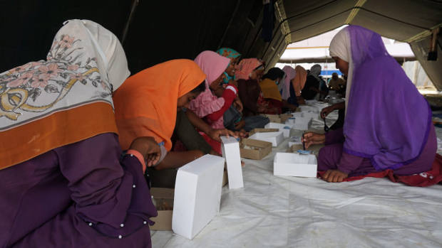A group of Rohingya eat meals provided by the local government in Lhokseumawe, Aceh province, a day after their arrival in Indonesia, Sept. 8, 2020. [Muzakir Nurdin/BenarNews]
