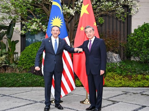 Malaysian Foreign Minister Hishammuddin Hussein (left) and his Chinese counterpart Wang Yi greet each other according to COVID-19 protocols, in Fujian province in China, April 2, 2021.