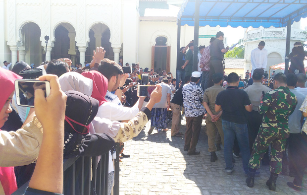 Aceh residents film a man being caned for violating Sharia law, outside a mosque in Banda Aceh, Indonesia, July 13, 2018. (Nurdin Hasan/BenarNews)
