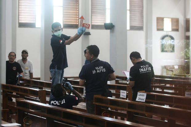 In this photograph shot through a glass window, police investigators examine the interior of St. Lidwina Church in Yogyakarta province, Indonesia, following an attack by a sword-wielding man during Sunday Mass, Feb. 11, 2018.