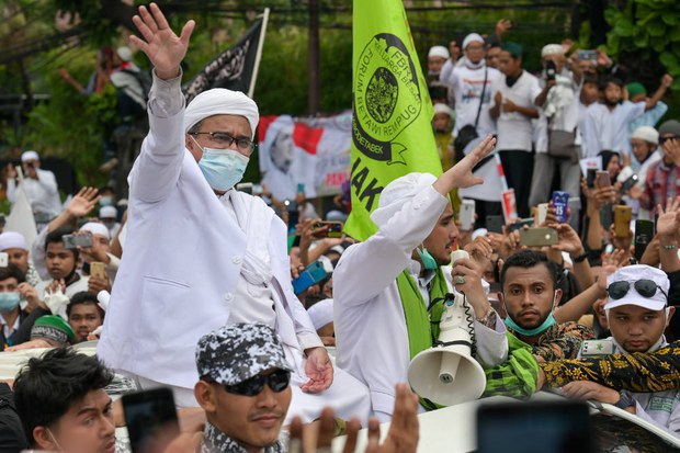 Rizieq Shihab (left), leader of the hardline Islamic Defenders Front (FPI), greets supporters at the organization's headquarters in Jakarta, following his return from Saudi Arabia, Nov. 10, 2020.