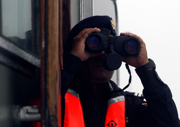 A crew member aboard a rescue ship scans the sea with binoculars during a search operation for the Lion Air plane crash in waters off Tanjung Karawang, Indonesia, Oct. 31, 2018. [AP]