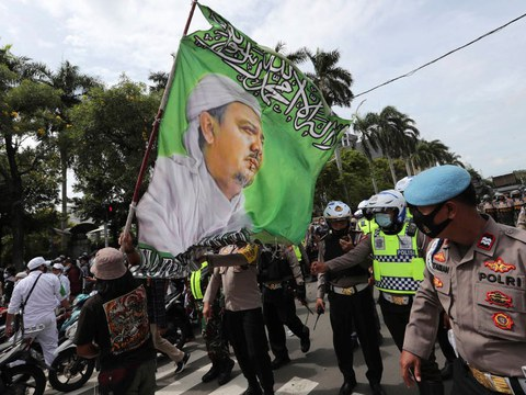 Supporters of Muhammad Rizieq Shihab, leader of the Islam Defenders Front, display a flag bearing his image during a rally in Jakarta, Indonesia, Friday, Dec. 18, 2020.
