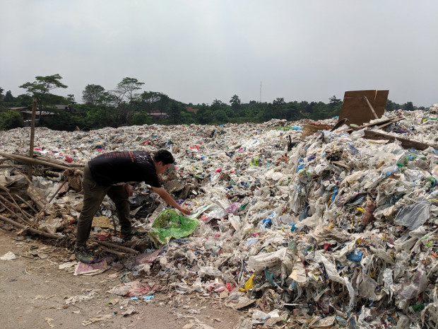 A man picks through plastic packaging in a dumpsite for imported plastic trash, in Bekasi, in Indonesia's West Java province, May 16, 2019. [Ahmad Syamsudin/BenarNews]