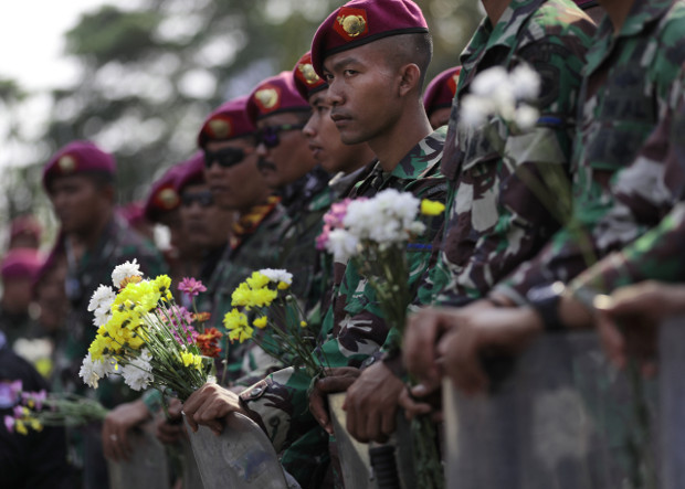 Indonesian marines hold flowers handed out by student protesters during a rally outside the parliament in Jakarta, Oct. 1, 2019. [AP]