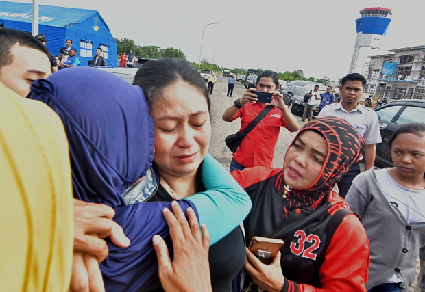 Putri (center), a woman whose husband and child were on board the crashed Lion Air flight, is consoled at Pangkal Pinang airport in Bangka Belitung province, Oct. 29, 2018. [AFP]