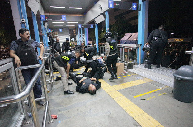 Police assist their colleagues who suffered injures during the clash with protesters in front of the of the Election Supervisory Agency headquarters in Jakarta, May 22, 2019. [Keisyah Aprilia/BenarNews]