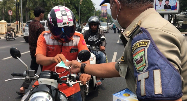 An Indonesian police officer hands out a face mask to a motorcycle rider in Padang, West Sumatra, Indonesia, Sept. 13, 2019. [Sulthan Azzam/BenarNews]