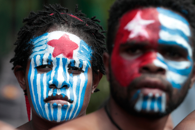 Papuan activists, their faces painted with the colors of the separatist Morning Star flag, attend a rally near the presidential palace in Jakarta, Aug. 22, 2019. [AP]