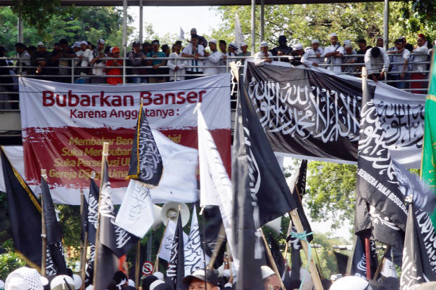 Muslim protesters hang banners, including one calling for Muslim paramilitary group Banser to be disbanded, during a rally in Jakarta, Oct. 26, 2018. (Arie Firdaus/BenarNews)