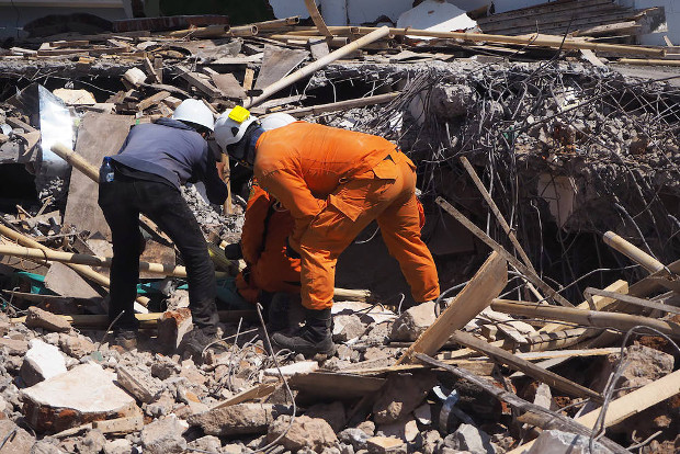 Rescuers search for survivors under concrete and twisted rebar of the Jabal Nur Mosque in Lading-Lading town of North Lombok, Indonesia, Aug. 7, 2018. [Anton Muhajir/BenarNews]