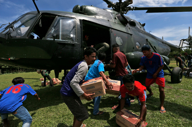 Earthquake survivors carry relief goods delivered by an Indonesian Army helicopter in Poroo, Central Sulawesi, Oct. 7, 2018. [AP]