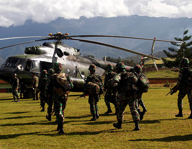 Indonesian soldiers carry rifles as they walk toward a helicopter to fly to Nduga district in Papua province, Dec. 5, 2018. [Antara Foto/Iwan Adisaputra via Reuters]