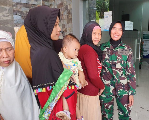 Tansya Susan, an Indonesian Navy sergeant, greets women and children waiting for medical care at the clinic outside of Jakarta, Aug. 6, 2019. (Ahmad Syamsudin/BenarNews)