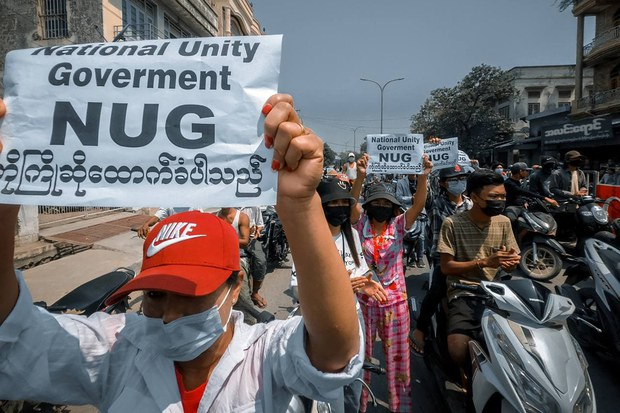 Protesters hold signs supporting the newly formed opposition National Unity Government as they demonstrate against the military coup in Shwebo, in Myanmar's Sagaing region, April 18, 2021.