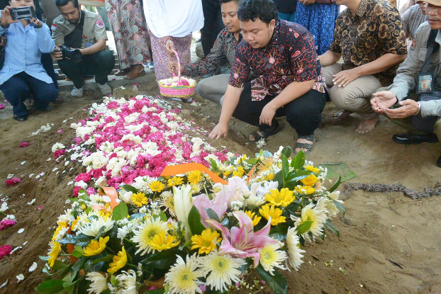 Muhammad Ivanka Rizaldy Nugroho prays at his father's grave, July 8, 2019. [Kusumasari Ayuningtyas/BenarNews]