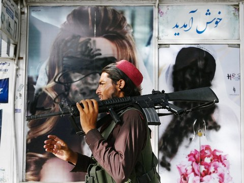 A Taliban fighter walks past a beauty salon with images of women defaced using a spray paint in Kabul, Aug. 18, 2021.