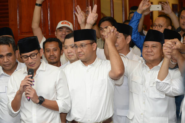Jakarta governor-elect Anis Baswedan (center), his deputy governor-elect Sandiaga Uno (left), and Prabowo Subianto (right), celebrate during a press conference in Jakarta on April 19, 2017. (AFP)